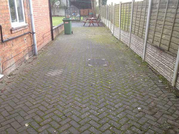 Block paved patio heavily infested with moss and lichen before cleaning